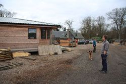 Maggie and Jim Birley at their community sawmill, with the house they built in the background